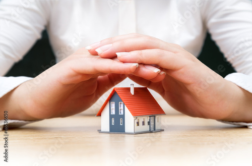 house covered of woman hands - insurance real estate concept poster