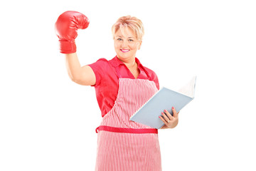 Mature woman with boxing glove holding a notebook