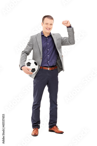 Young football fan cheering with ball in hand