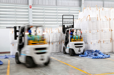 worker driving a forklift loader in warehouse with load jumbo ba