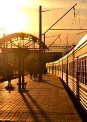 Train leaving the railway station at sunset