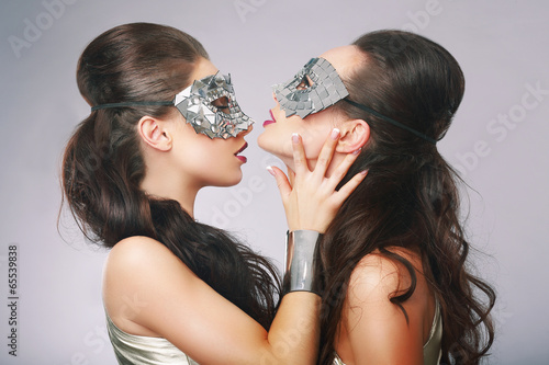 Performance. Fancy Women in Surrealistic Stylized Silver Masks