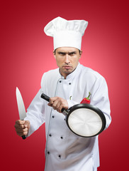 Funny portrait of a chef with a knife and a pan in his hands