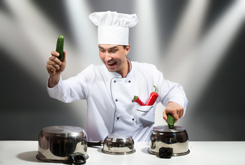 Chef drumming on pots with cucumbers, with stage lights