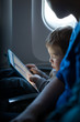 Leinwanddruck Bild - Little boy playing with a tablet in an airplane