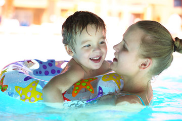 Mother and her son in the outdoor swimming pool