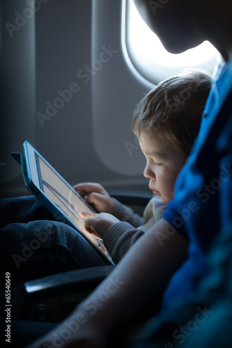Leinwanddruck Bild Little boy playing with a tablet in an airplane