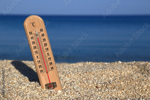 Leinwanddruck Bild Thermometer on a beach shows high temperatures