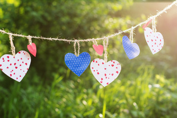 Colorful hearts hanging on green background