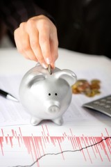 Female hand putting coin in piggy bank, on the office desk.