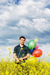 Young man in a spring field with lots of balloons