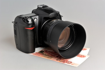 Photo camera with money on gray