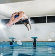 Young muscular swimmer jumping from starting block