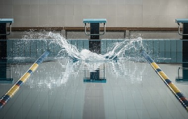 Splashes after swimmers jump in a swimming pool