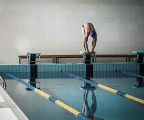 Young muscular swimmer on starting block in a swimming pool