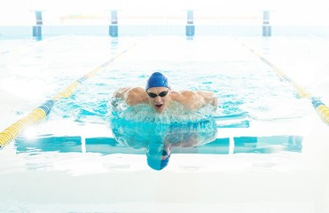 Young man using breaststroke technique