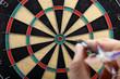 hand throwing dart to dartboard - 65544240