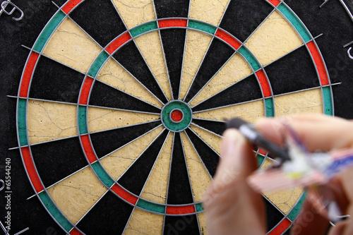 hand throwing dart to dartboard