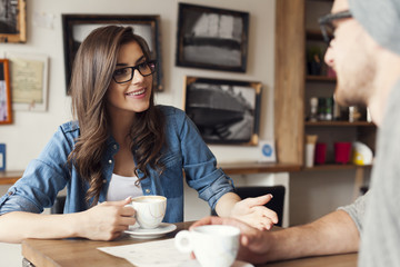 Hipster couple talking at cafe