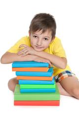Pensive young boy near books