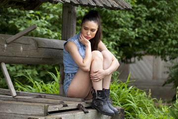 Beautiful young woman sits on a wooden pit in the park