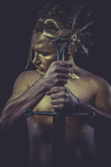 Man with body painted gold feather mask and steel sword