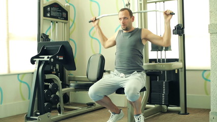 Young man exercising with body building equipment in the gym
