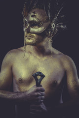 Greek man with body painted gold feather mask and steel sword