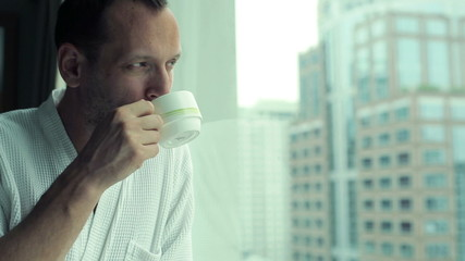 Man in bathrobe drinking coffee, looking at cityscape