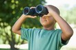 Little boy looking up through binoculars in the park - 65552832