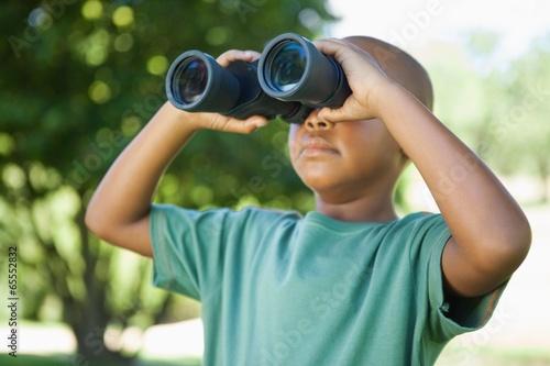 Little boy looking up through binoculars in the park - 65552832