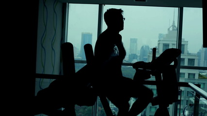 Silhouette of man riding stationary bike in the gym