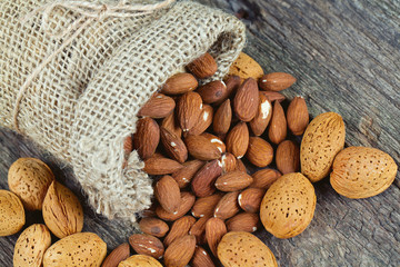 almonds in a  burlap bag on wooden surface