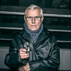 Senior man aiming a gun
