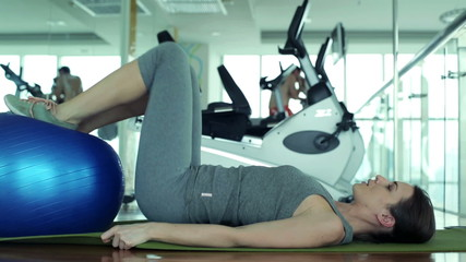 Young fit woman working with fitness bal in the gym