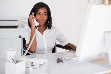 Happy businesswoman in wheelchair working at her desk