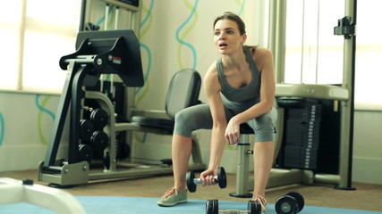 Young fit woman exercising with dumbbel in the gym