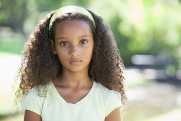 Young girl frowning at the camera in the park