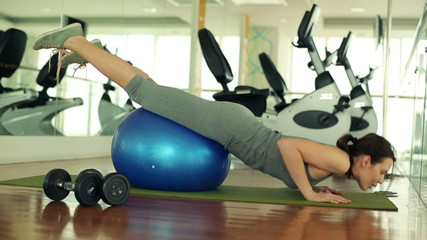 Young woman doing push-ups on fitness ball in the gym