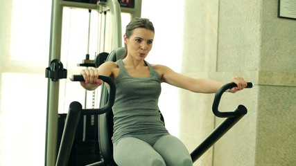 Young woman exercising on rowing machine in the gym
