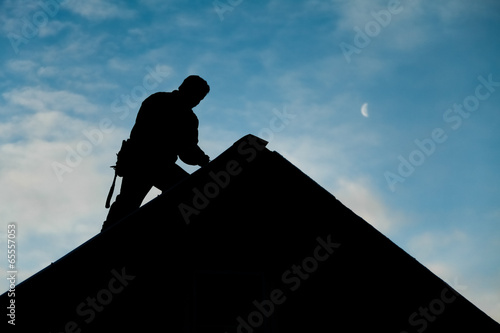 Contractor in Silhouette working on a Roof Top - 65557053