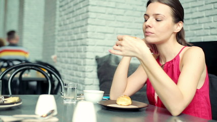Woman eating tasty sweet bun in cafe