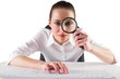 Businesswoman typing and looking through magnifying glass