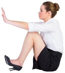 Businesswoman sitting on floor pushing