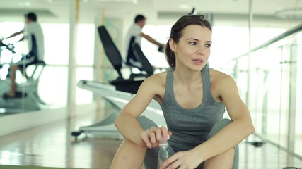 Young fit woman drinking water and resting after workout in gym