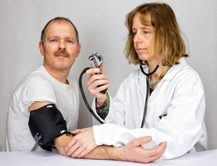 Female doctor checks blood pressure of a patient