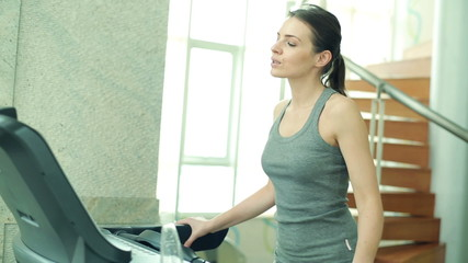 Woman drinking water while walking on treadmill machine in gym