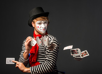 Clown throws playing cards