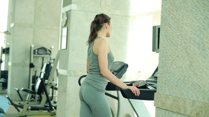 Young fit attractive woman walking on treadmill machine in gym