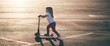 Fototapety Little beautiful girl riding a scooter